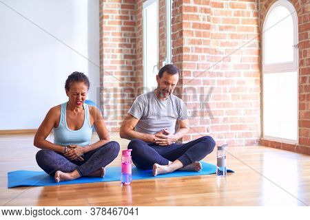 Middle age sporty couple sitting on mat doing stretching yoga exercise at gym with hand on stomach because indigestion, painful illness feeling unwell. Ache concept.