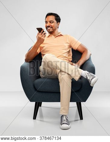 people, technology and communication concept - happy smiling young indian man sitting in chair calling on smartphone or using voice command recorder over grey background