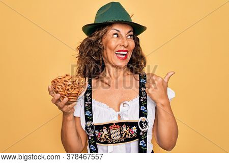 Middle age woman wearing traditional octoberfest dress holding bowl with baked pretzels pointing and showing with thumb up to the side with happy face smiling