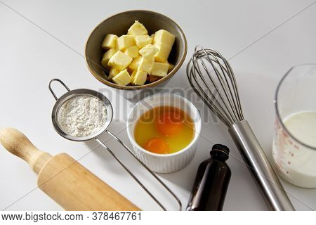 cooking food and culinary concept - rolling pin, butter, eggs, flour and whisk on table