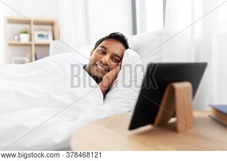 people, bedtime and rest concept - happy smiling indian man looking at tablet pc computer lying in bed at home