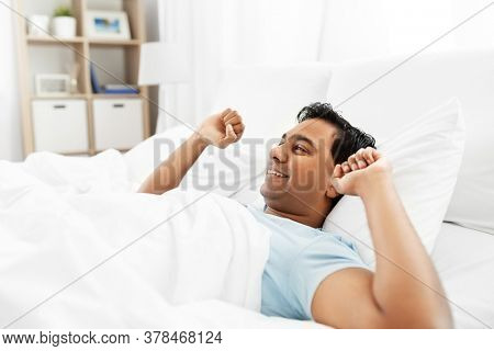 people, bedtime and rest concept - happy smiling indian man stretching in bed at home