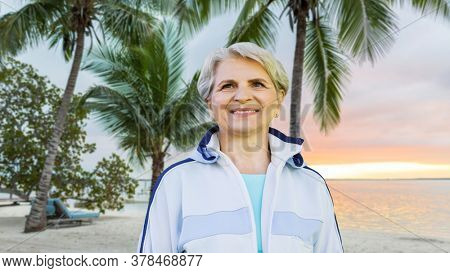 fitness, sport and healthy lifestyle concept - smiling sporty senior woman over tropical beach background in french polynesia
