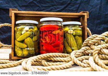 Glass Jars With Pickled Red Bell Peppers And Pickled Cucumbers (pickles) Isolated In Wooden Crate. J