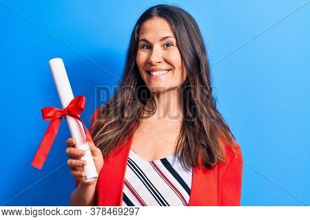 Young beautiful brunette smart woman holding graduated degree diploma over blue background looking positive and happy standing and smiling with a confident smile showing teeth