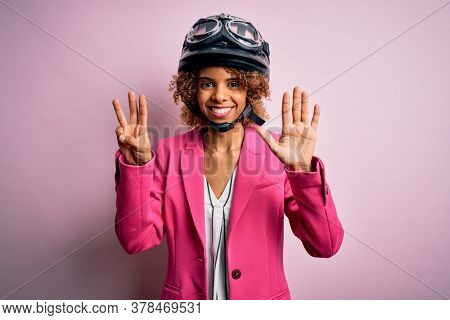 African american motorcyclist woman with curly hair wearing moto helmet over pink background showing and pointing up with fingers number eight while smiling confident and happy.