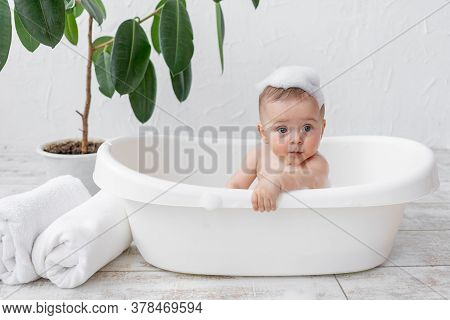 A Small Child Boy 8 Months Old Bathes In A Bath With Foam And Soap Bubbles, Place For Text