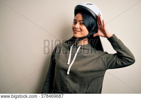Young beautiful chinese woman wearing bike helmet over isolated white background smiling with hand over ear listening an hearing to rumor or gossip. Deafness concept.