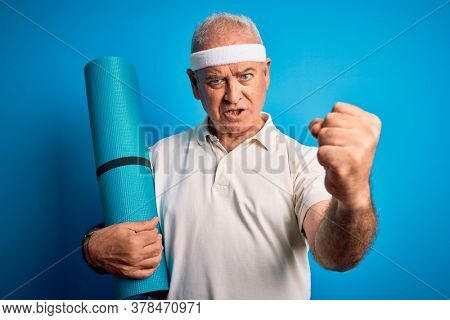 Middle age hoary sportsman holding yoga mat over isolated blue background annoyed and frustrated shouting with anger, crazy and yelling with raised hand, anger concept