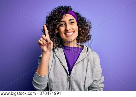 Beautiful curly arab sportswoman doing sport wearing sportswear over purple background showing and pointing up with finger number one while smiling confident and happy.