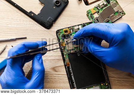 Technician Repairing Mobile Phone At Table, Closeup