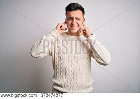 Young handsome caucasian man wearing casual winter sweater over white isolated background covering ears with fingers with annoyed expression for the noise of loud music. Deaf concept.