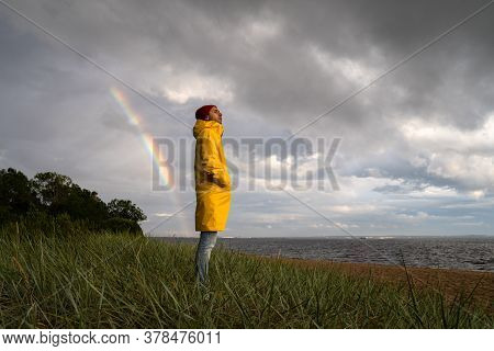 Man In Yellow Raincoat Wear Red Hat Standing On The Beach In Rainy Weather, Looks At Dramatic Cloudy