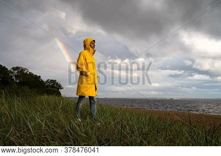 Man In Yellow Raincoat With Hood Walk On The Beach In Rainy Weather, Looks At Dramatic Cloudy Sky An