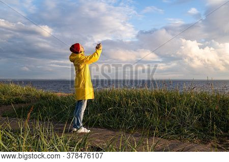 Man In Yellow Raincoat Wear Red Hat Standing On The Beach At Wooden Path, Looks At Dramatic Cloudy S