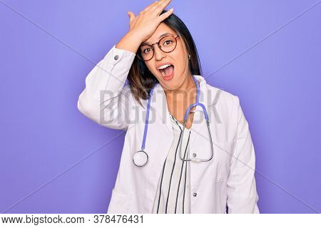 Professional doctor woman wearing stethoscope and medical coat over purple background surprised with hand on head for mistake, remember error. Forgot, bad memory concept.