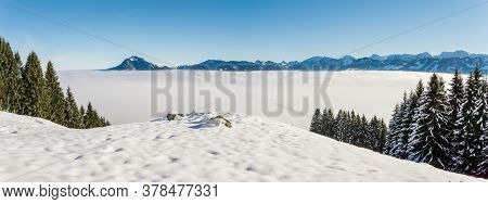 Amazing Winter Panoramic View To Snowy Mountain Range Above Inversion Fog Clouds With Forest Trees.