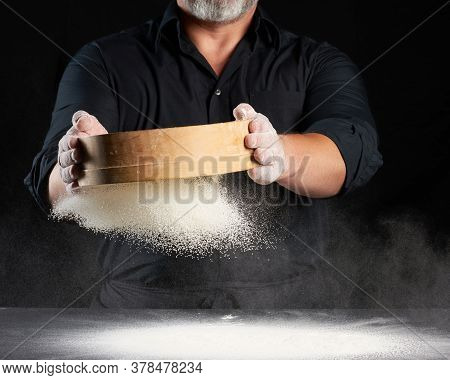 Chef A Man In A Black Uniform Holds A Round Wooden Sieve In His Hands And Sifts White Wheat Flour On