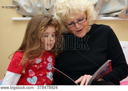 A Grandmother Reads A Bedtime Story To Her Granddaughter, Taken 24th December 2009 In Witney, Oxford
