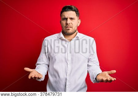 Young business man with blue eyes wearing elegant shirt standing over red isolated background clueless and confused with open arms, no idea concept.