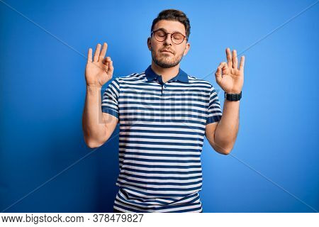 Young man with blue eyes wearing glasses and casual striped t-shirt over blue background relax and smiling with eyes closed doing meditation gesture with fingers. Yoga concept.
