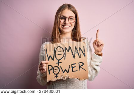 Young beautiful redhead woman asking for women rights holding banner over pink background surprised with an idea or question pointing finger with happy face, number one
