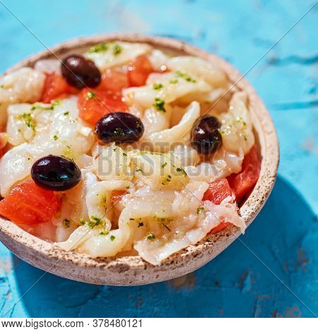 closeup of a plate with esqueixada de bacalla, a cold dish made with codfish, tomato, onion and black olives, and dressed with olive oil, typical of Catalonia, Spain, on a blue rustic surface