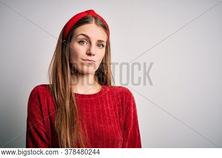 Young beautiful redhead woman wearing red casual sweater and diadem over yellow background Relaxed with serious expression on face. Simple and natural looking at the camera.
