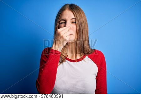 Young beautiful redhead woman wearing casual t-shirt over isolated blue background smelling something stinky and disgusting, intolerable smell, holding breath with fingers on nose. Bad smell