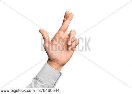 Hand of caucasian young man showing fingers over isolated white background gesturing fingers crossed, superstition and lucky gesture, lucky and hope expression