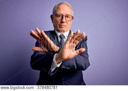 Grey haired senior business man wearing glasses and elegant suit and tie over purple background Rejection expression crossing arms doing negative sign, angry face