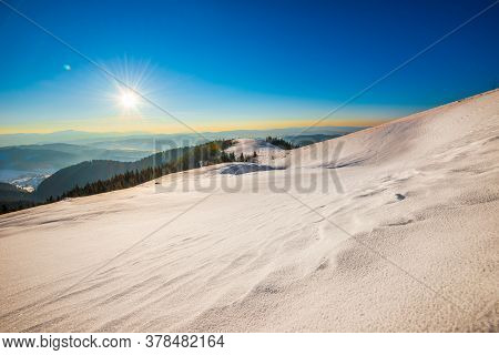 Beautiful Bewitching View Of Mountain Slopes With Dense Thickets Of Trees And Snowdrifts Against The