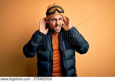 Young handsome skier man with beard wearing snow sportswear and ski goggles Trying to hear both hands on ear gesture, curious for gossip. Hearing problem, deaf