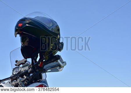 Motorcycle Helmet. Helmet For Moto On The Background Of Nature. A Black Helmet Hangs On A Motorcycle