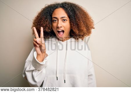 Young african american sportswoman with afro hair wearing sporty sweatshirt showing and pointing up with fingers number two while smiling confident and happy.