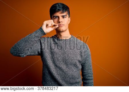 Young handsome man wearing casual sweater standing over isolated orange background mouth and lips shut as zip with fingers. Secret and silent, taboo talking