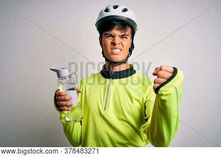 Young handsome cyclist man wearing security bike helmet drinking bottle of water annoyed and frustrated shouting with anger, crazy and yelling with raised hand, anger concept