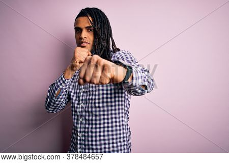 Young handsome african american afro man with dreadlocks wearing casual shirt Punching fist to fight, aggressive and angry attack, threat and violence