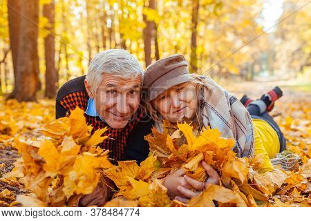 Fall Family Activities. Senior Man And Woman Lying On Heap Of Leaves In Autumn Park. People Having F
