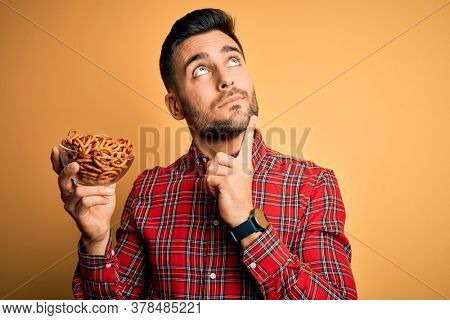Young handsome man holding bowl with baked German pretzels over yellow background serious face thinking about question, very confused idea