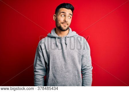 Young handsome sportsman wearing sweatshirt standing over isolated red background smiling looking to the side and staring away thinking.