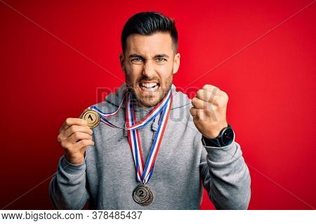 Young handsome succesful man winning medals standing over isolated red background annoyed and frustrated shouting with anger, crazy and yelling with raised hand, anger concept