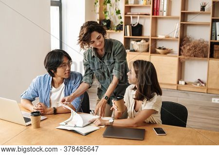 Image of multinational cheerful colleagues discussing project while working with laptops in office