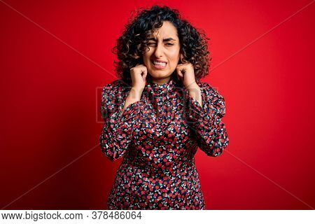Young beautiful curly arab woman wearing casual floral dress standing over red background covering ears with fingers with annoyed expression for the noise of loud music. Deaf concept.