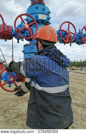 Two Drilling Crew Workers Dismantle The Bottom Of The Drill String. Unscrewing The Spiral Calibrator