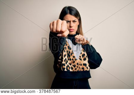 Young beautiful woman wearing casual sweatshirt standing over isolated white background Punching fist to fight, aggressive and angry attack, threat and violence