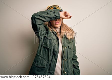 Young brunette skier woman wearing snow clothes and ski goggles over white background covering eyes with arm, looking serious and sad. Sightless, hiding and rejection concept