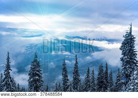 Breathtaking Landscape With High Mountains On The Hills And Slopes In A Snowy Forest Against The Sky