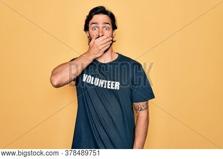 Young handsome hispanic volunteer man wearing volunteering t-shirt as social care shocked covering mouth with hands for mistake. Secret concept.