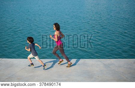 Jogging Boy With Mom. A Child Runs On Distillation With His Mother. A Woman And Her Son Run Along Th